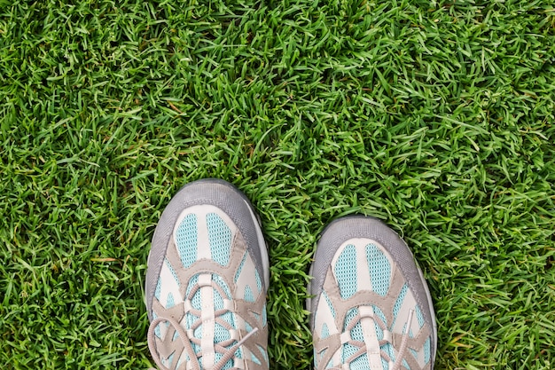 Old travel sneakers on the green grass