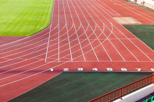 Старый стадион беговой дорожки - сфотографированный крупный план старой оранжевой беговой дорожки на стадионе