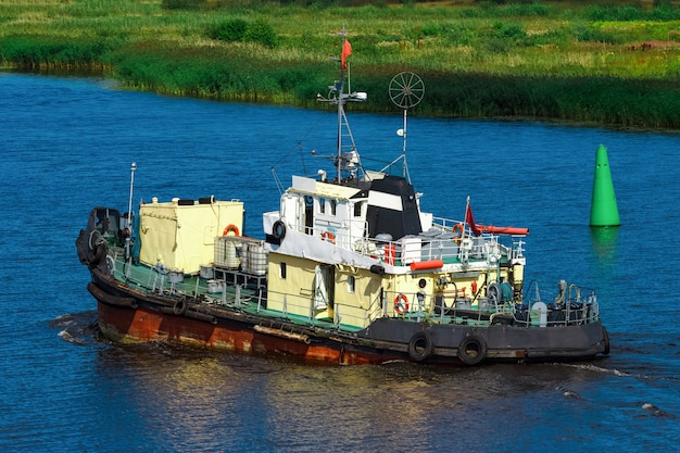Old tug ship moving to the cargo terminal. industrial service