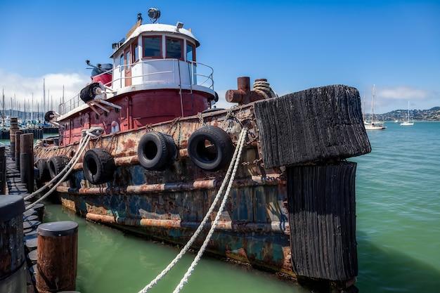 Старый буксир пришвартован у пристани в саусалито