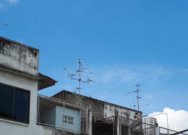 На городском доме установлена старая телевизионная антенна. изображение устройства связи.
