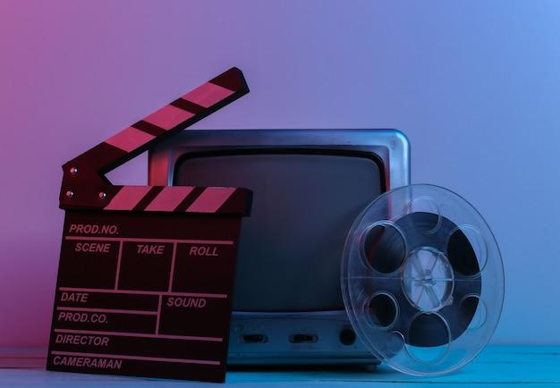 映画のカチンコ、赤青ネオンライトのフィルムリールを備えた古いテレビ受信機。エンターテインメント業界