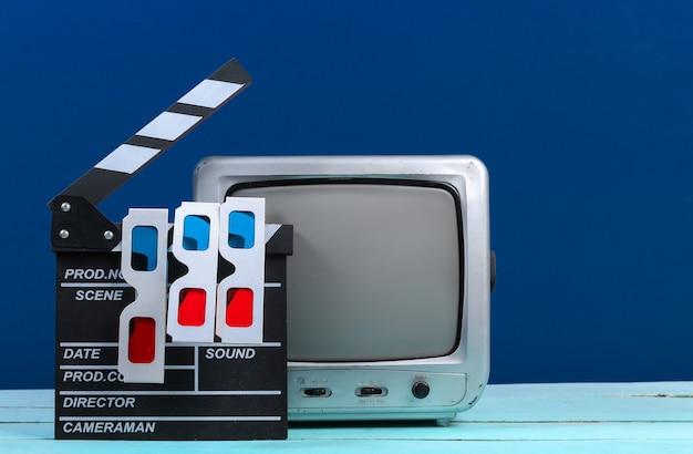 映画のカチンコ、クラシックブルーの3dメガネを備えた古いテレビ受信機。エンターテインメント産業、メディア、映画製作