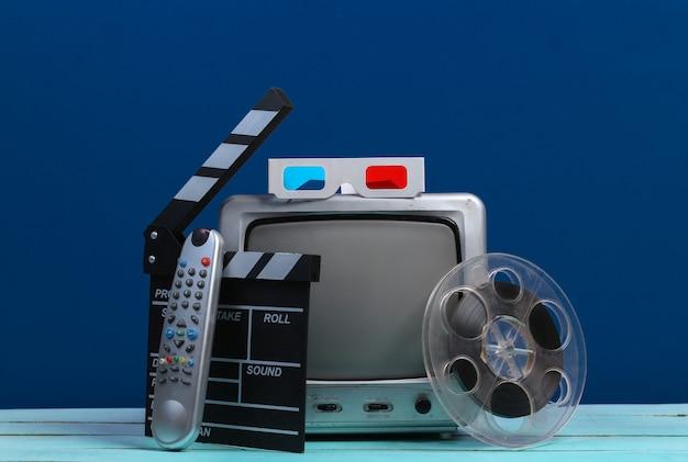 映画のカチンコ、フィルムリール、クラシックブルーの3dメガネを備えた古いテレビ受信機。エンターテインメント産業、メディア、映画製作
