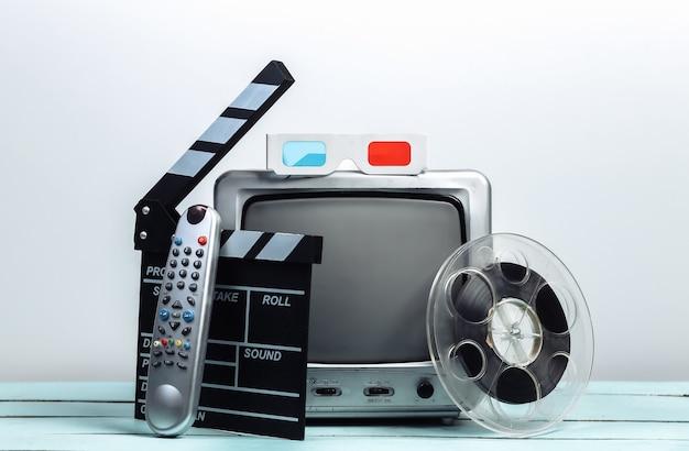 映画のカチンコ、フィルムリール、白い壁に3dメガネを備えた古いテレビ受信機。エンターテインメント産業、メディア、映画製作