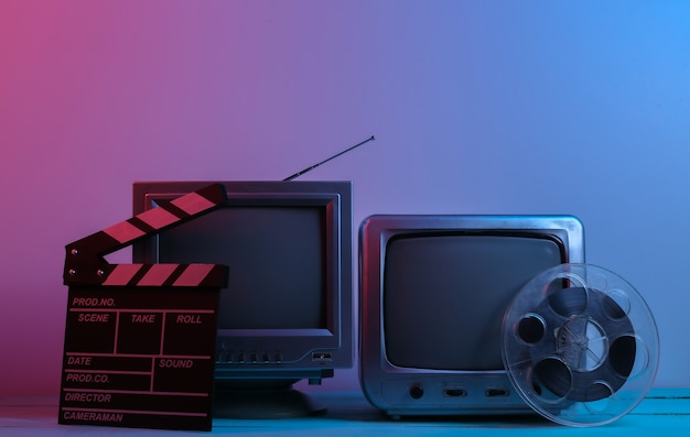 映画のカチンコ、赤青のネオンライトのフィルムリールを備えた古いテレビ受信機。エンターテインメント業界 Premium写真