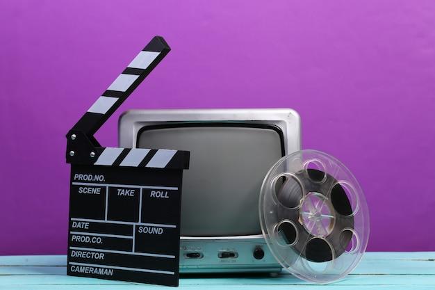 映画のカチンコ、紫色のフィルムリールを備えた古いテレビ受信機。エンターテインメント産業、メディア、映画製作