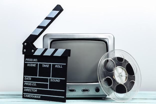 映画のカチンコ、白い壁にフィルムリールを備えた古いテレビ受信機。エンターテインメント産業、メディア、映画製作
