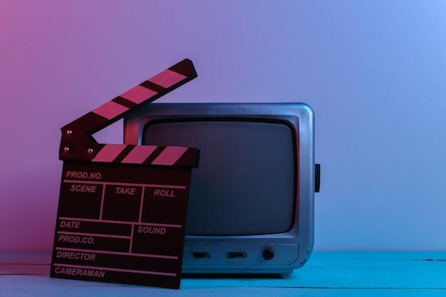 赤青ネオンライトの映画カチンコを備えた古いテレビ受信機。エンターテインメント業界