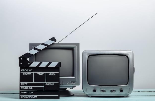 白い壁に映画のカチンコが付いている古いテレビ受信機。エンターテインメント業界、メディア