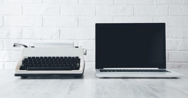 机の上の古いタイプライターとラップトップ