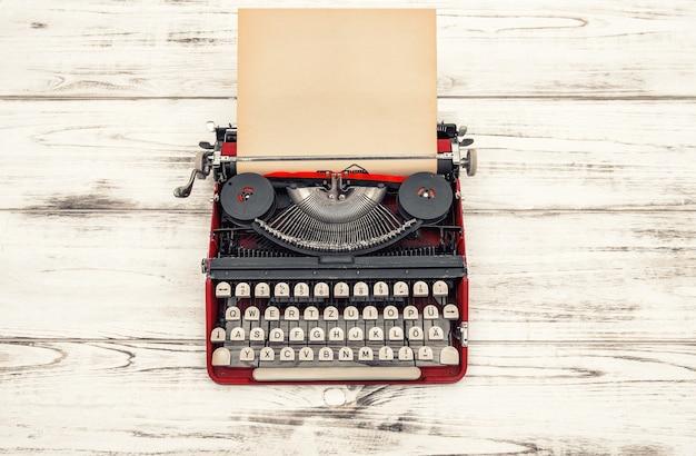 Старая пишущая машинка на деревянном столе. антикварный объект. винтажный стиль тонированное изображение. немецкая надпись