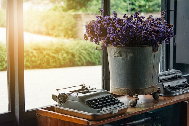 Old typewriter vintage ornaments and vases of purple flowers on a wooden table.