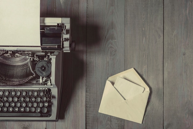 An old typewriter with a sheet of paper and an open envelope with a letter lie on a wooden table