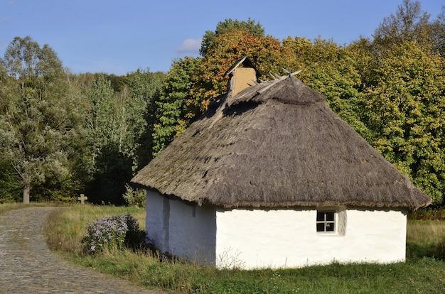 Старый украинский дом с крестом на заднем плане