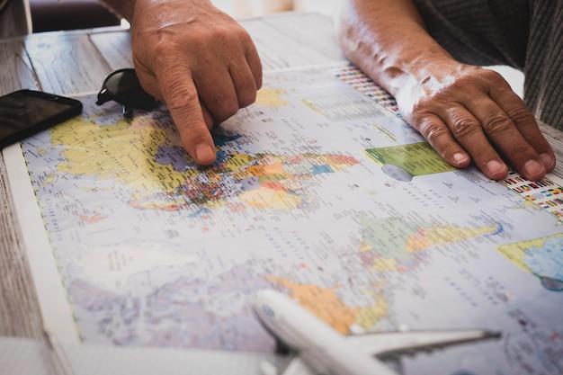 새로운 여행을 계획하고 있는 알아볼 수 없는 오래된 사람들 - 방랑벽 생활을 위한 나이 제한 없음 - 백인 부부와 탁자 위에 비행기 장난감이 있는 세계 지도 - 여행자와 휴가
