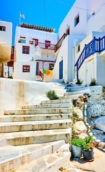 그리스 미코노스에 흰색 작은 집이 있는 오래된 오르막 거리