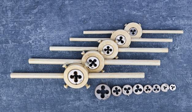 Старый использованный комплект для нарезания внешней резьбы, крупный план, вид сверху, стилизованный, плашки для нарезания резьбы