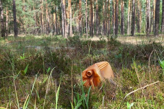 Старая использованная пластиковая канистра для горюче-смазочных материалов лежит в траве на лесной поляне