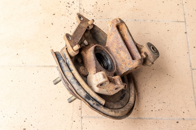 Old, used, rusty rear hub, inner part without brake disc, on the beige tiled floor of the workshop