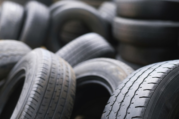 Old used tires stacked with high piles. close up damaged worn black tire tread car.