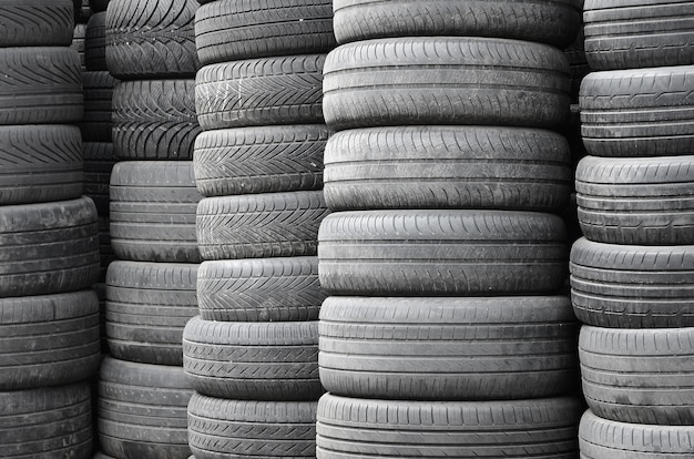 Old used tires stacked with high piles in secondary car parts shop garage