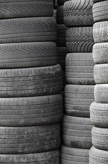 Old used tires stacked with high piles in secondary car parts shop garage Premium Photo