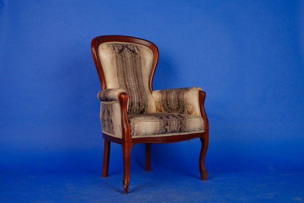 Old velour retro chair on blue royal background without interior. antique brown upholstered sofa for an elegant living room. vintage designer chair on dark background. classic style. copy space