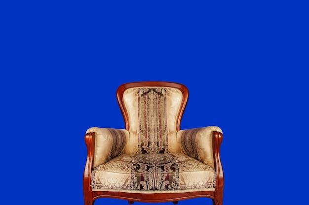 青いロイヤルの背景に古いベロアのレトロな椅子