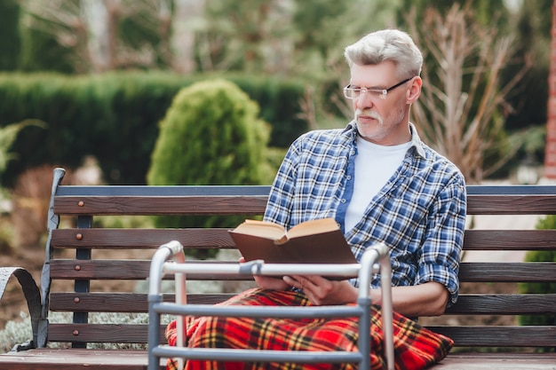 Old veteran reading a book while siting on garden
