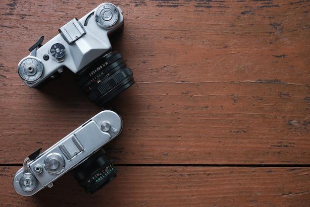 古いヴィンテージ35mm金属フィルムカメラ、クローズアップ。テキスト用のスペース。上面図。粗い木の表面は茶色です。 Premium写真