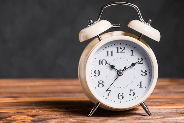 An old vintage alarm clock on wooden desk against black background
