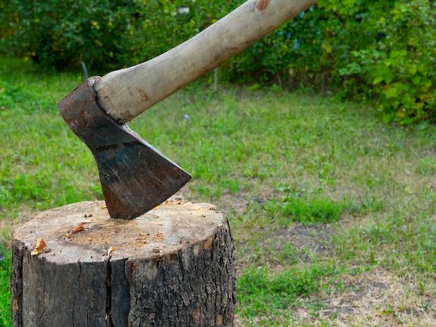 他の木の丸太を切り刻むために使用される木の丸太で立ち往生している古いヴィンテージの斧