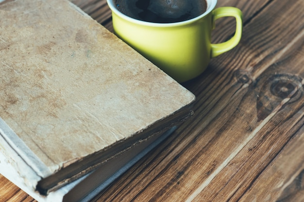 Old vintage battered books and a cup of coffee