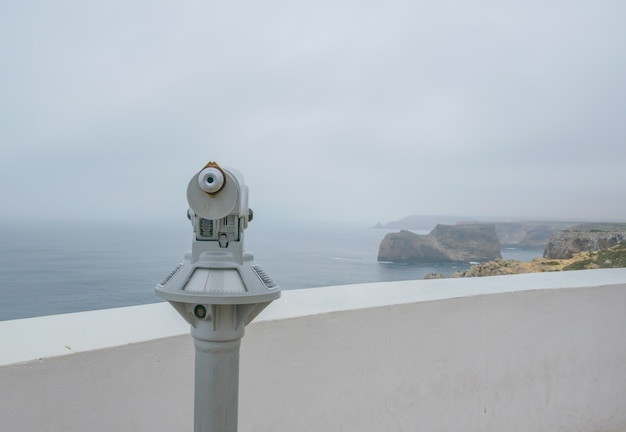 Old vintage binocular on the deck with a cloundy view with sea