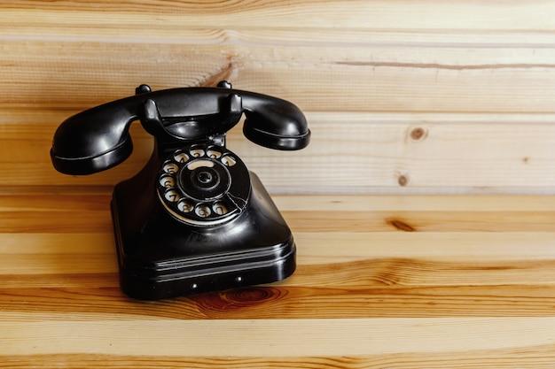 木製のテーブルの上の古いヴィンテージの黒い電話。