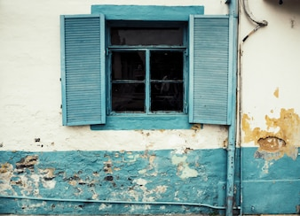 Old vintage blue wooden window Greece style white concrete background