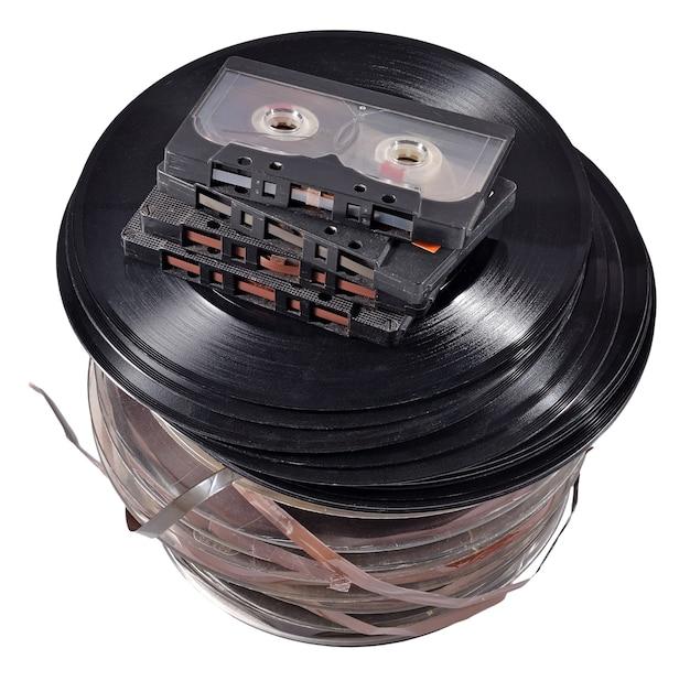 白い背景の上の古いヴィンテージボビン、ビニールレコード、カセットテープ
