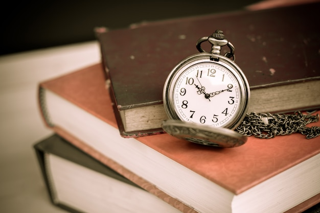 Old vintage books and pocket watches on wooden desk. retro style filtered photo