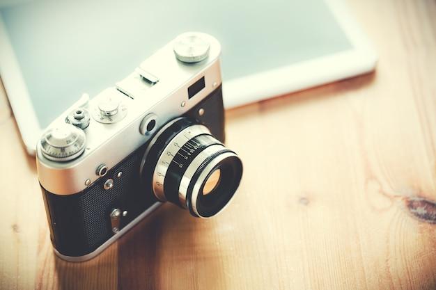 Старый старинный фотоаппарат с планшетом на деревянном столе.