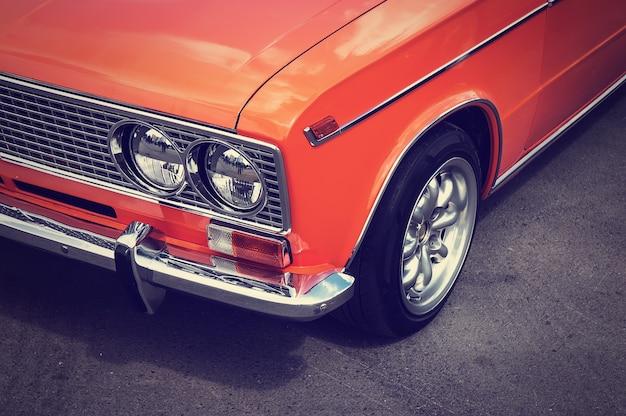 Старый винтажный автомобиль оранжевого цвета на сером асфальте