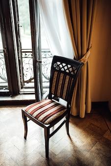 창 근처 오크 바닥에 오래 된 빈티지 의자