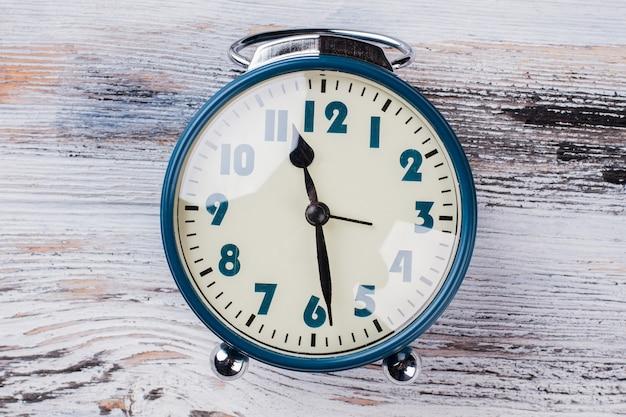白い木製の背景に古いヴィンテージ時計。青いレトロな目覚まし時計を閉じます。午後6時または午前。