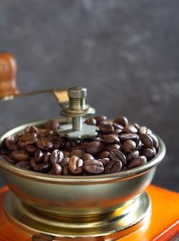 오래 된 빈티지 커피 분쇄기와 돌 벽 배경 질감 근처 콩