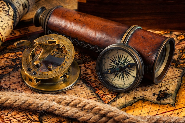 Old vintage compass and navigation instruments on ancient map