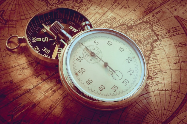 Old vintage compass and travel instruments on ancient map