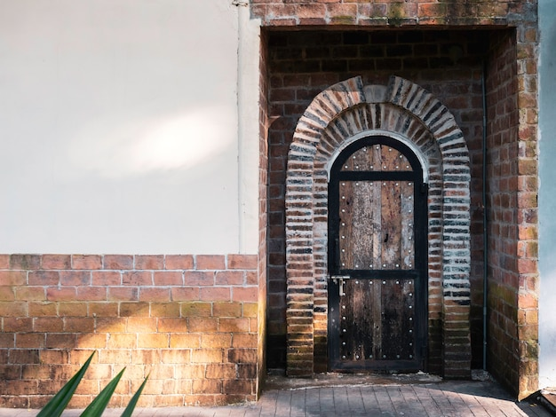 Old vintage curved wooden door ornamented with bricks on concrete building with copy space.