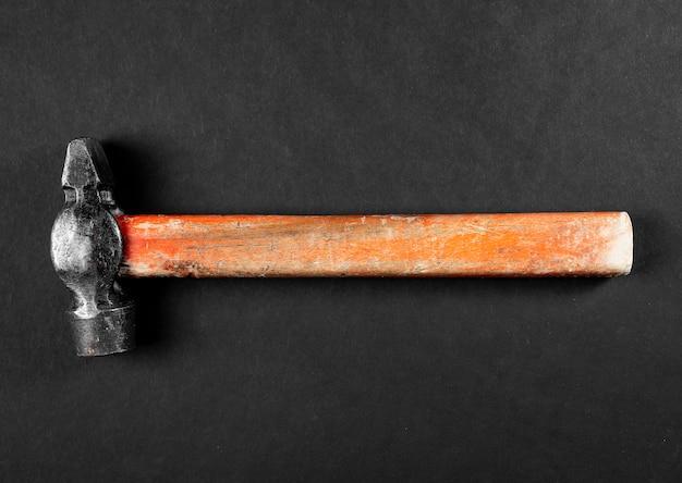 Старый старинный молоток с металлической головкой и деревянной ручкой на черном фоне, плоская планировка.