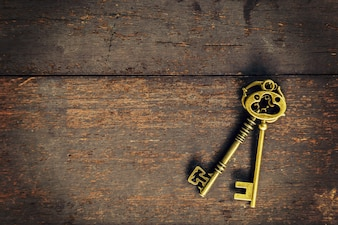 Old vintage key on wood texture background with space