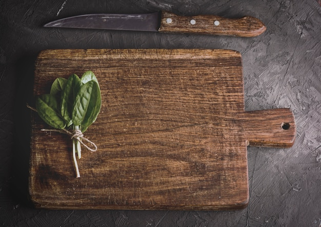 Old vintage kitchen cutting board and bunch with green sorrel leaves, top view
